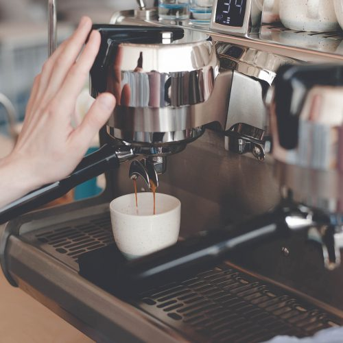 Hand Barista touches the coffee machine that makes espresso